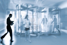 9787643-intentional-motion-blurred-image-of-a-business-group-walking-in-office-lobby-and-through-revolving-d.jpg